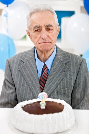 Senior man sitting front of birthday cake with candle in the form of questionnaires photo
