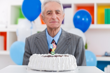 senior man with birthday cake with a question mark candle on it  photo
