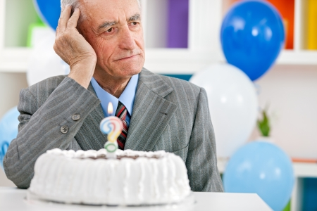 Senior man zit tegenover verjaardagstaart en proberen te herinneren hoe oud is Stockfoto