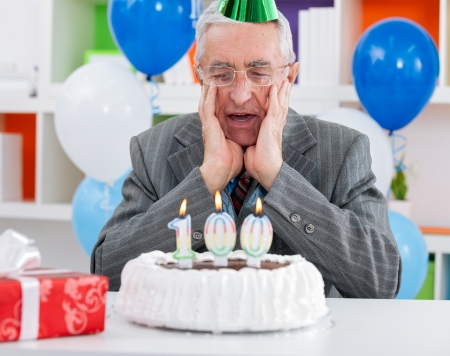 surprised senior man looking at birthday cake, so soon these years photo