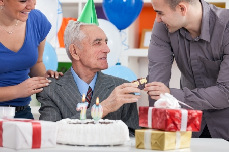 70 year old man: Senior man celebrating his birthday with family and cake with  candles  Stock Photo