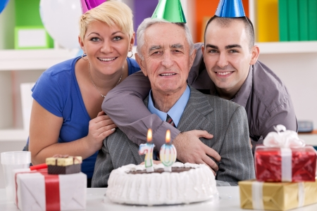 blow out:  Senior man celebrating his birthday with family, ready to blow out the many candles on his cake.