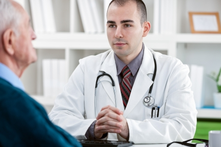 talks:  doctor talks to a male patient in his late 70s early  Stock Photo