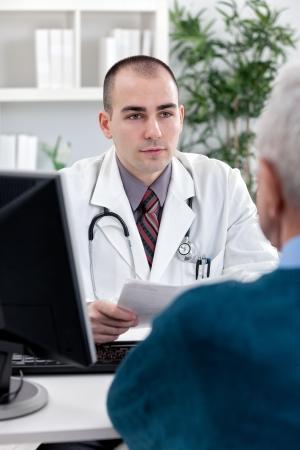 Knappe dokter met een patiënt op kantoor