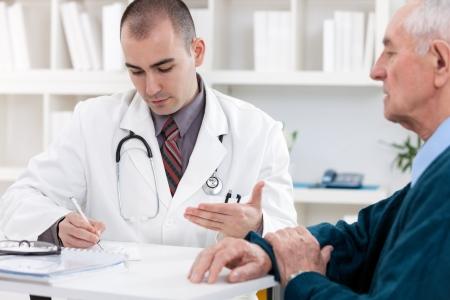 recetas medicas: Retrato de guapo masculino m�dico hablando con paciente senior Foto de archivo