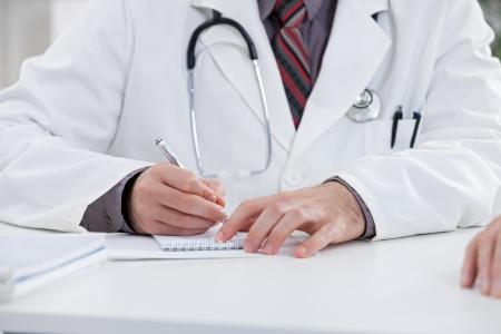Doctor que escribe una prescripción. Foto de archivo