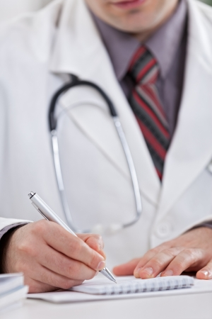 doctor writing:  Medical doctor writing a prescription