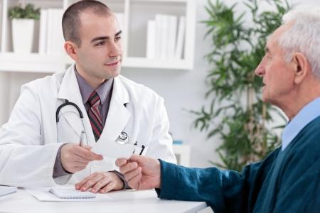 registration:  Male doctor giving   a prescription at patient