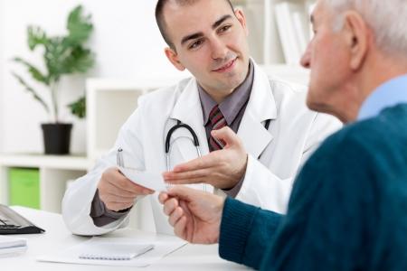 pharmacist: doctor showing  a prescription his patient