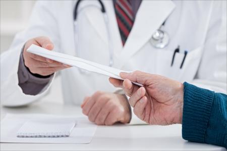 patient bribing doctor, giving money in envelope  photo