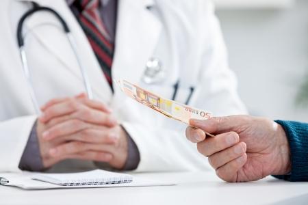 patient bribing doctor, giving money photo