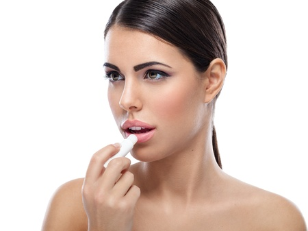 woman applying balsam on lips photo