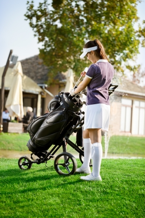 arranging:   Satisfied woman arranging your golf equipment after golf course
