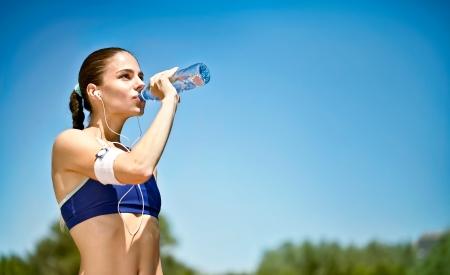 sudando: Mujer atleta toma un descanso, que el agua potable, en una carrera en un d�a caluroso Foto de archivo
