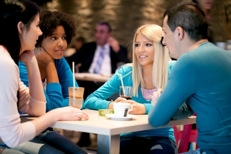 Group of teenagers in a cafe enjoy drinking  coffee photo