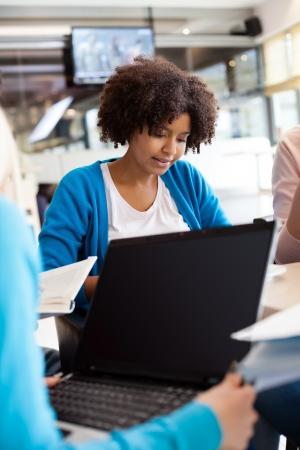 cafe internet: Afro Mujer joven con ordenador portátil en el café
