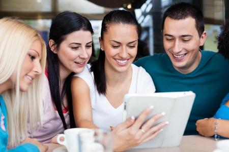 internet cafe: adolescentes felices que usa la tableta digital en cafe