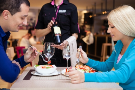 young couple nice dinner in a restaurant - waiter offers wine photo