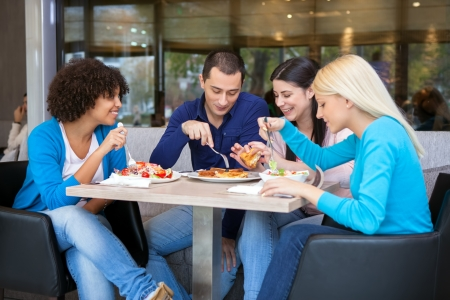 lunch meeting: Cheerful teenagers having lunch in restaurant, smiling and talking