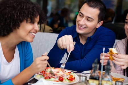 young affectionate couple having lunch in restaurant with friends photo