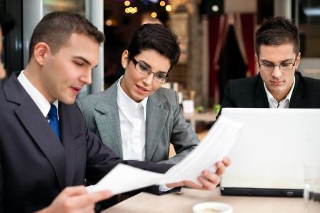 business team of three sitting in cafe and planning work  Stock Photo - 21260053