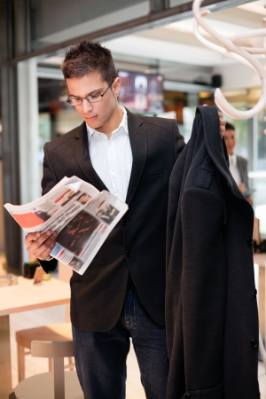concerted:  business young man  concerted  reading the newspaper while attaching his coat, interesting news