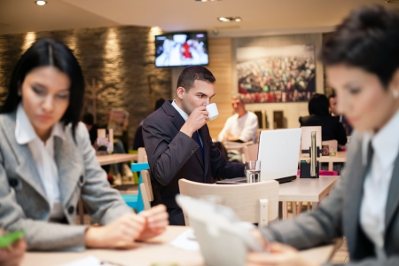 beauty shop:  Businessman sitting alone in a cafe  with a coffee and reading the newspaper Stock Photo