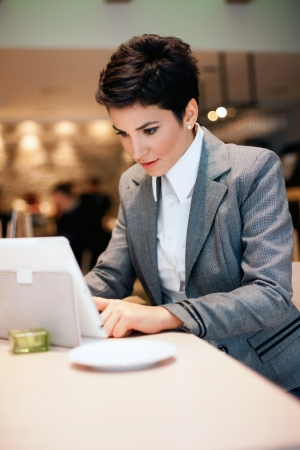 Young woman working on  tablet in cafe photo