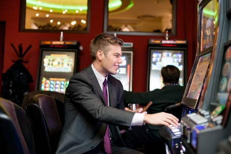 Happy man gambling on slot machine in casino  photo