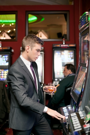 Handsome young gambling man on the slot machine in casino photo