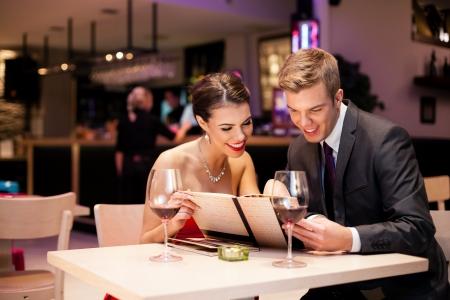 diner romantique: Couple lecture à Menu ensemble dans un restaurant Banque d'images