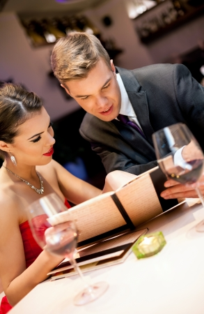 Couple choosing meal from the menu card in restaurant photo