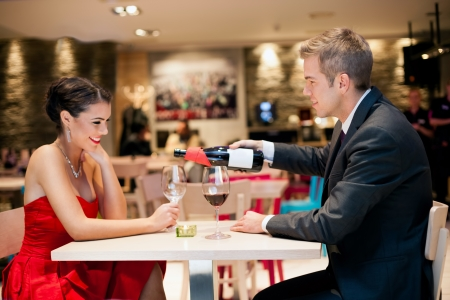 Gentlemen poured wine into a wine glass at a romantic dating photo