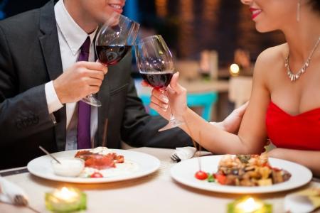 cena romantica: Mano che tiene un bicchiere di vino rosso e tostatura, celebrazione