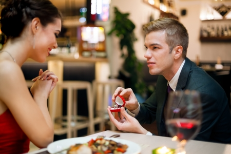 Man proposing to his girlfriend while they are having a romantic date at the restaurant photo