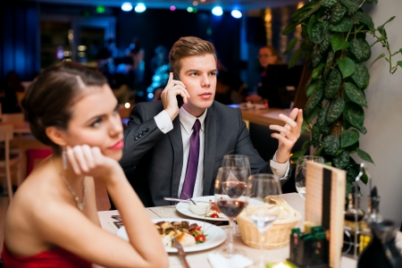 Man talking on a cell phone while on a date with his girlfriend or wife photo