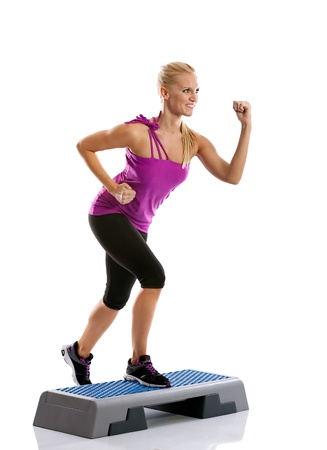 Beautiful blond young woman performing step aerobics exercise