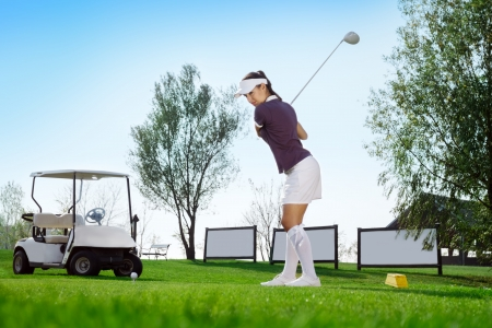 Attractive woman golfer hitting golf bag  photo