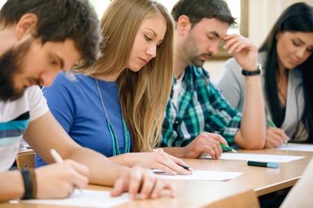 alumnos estudiando: Los jóvenes estudiantes que tienen una prueba en un aula Foto de archivo