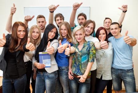 Groep van studenten aan de universiteit met duimen omhoog