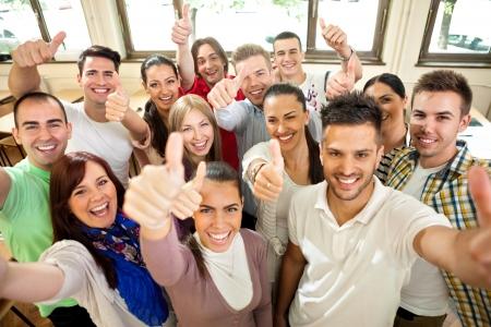 上げられた手と幸福の学生のグループ