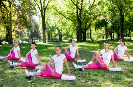 six girls: group of a young women performing stretches outdoors on a sunny day