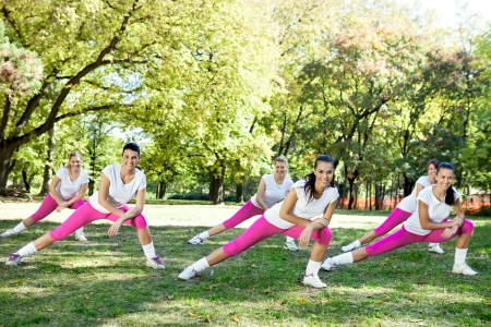 Group of six woman stretching legs, outdoor  photo