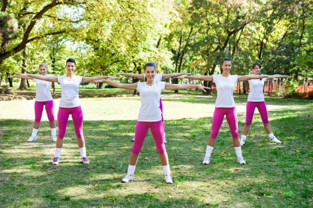 Group of six women doing fitness and lifting their arms photo