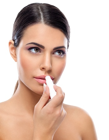 Young woman applying balsam on lips photo