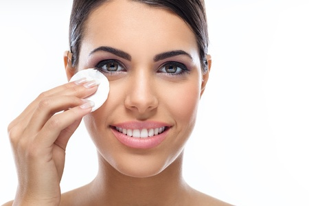 remover: Beautiful woman cleaning her pretty face with cotton swab - over white background