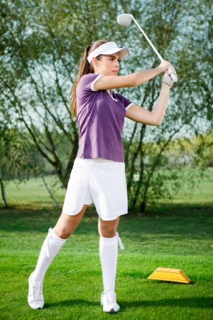 Girl golf player hitting ball on golf course  photo
