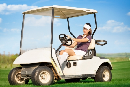Young attractive woman driving golf cart photo