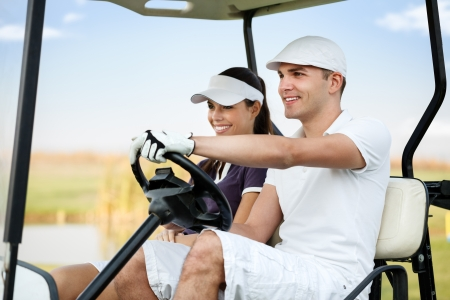 Happy young couple driving in golf cart  photo
