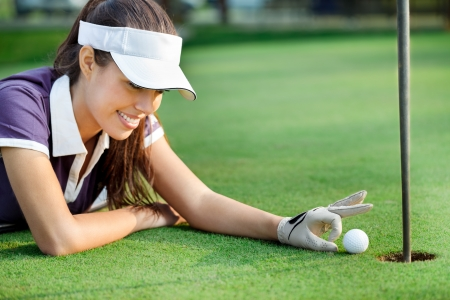Female golfer pushing ball in hole, sporting cheat Stock Photo